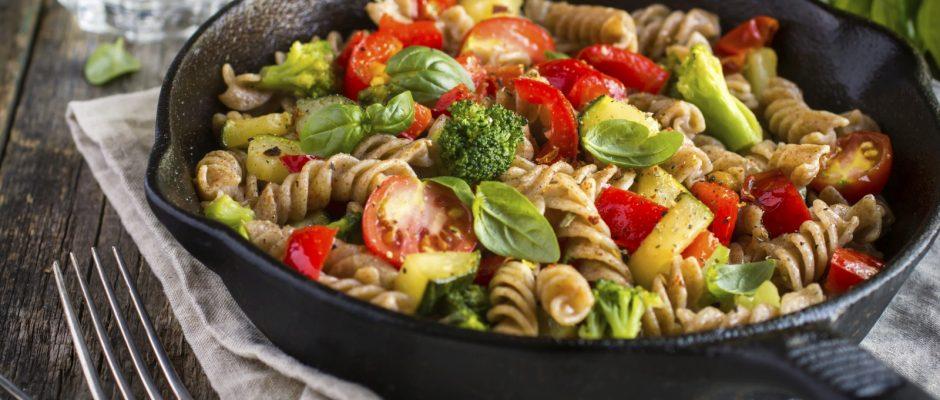 Eine Schale mit Pasta, Tomaten und Basilikum auf einem Holztisch umgeben von verschiedensten Zutaten.